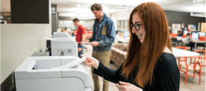 menina imprimindo em uma impressora multifuncional em local de estudo