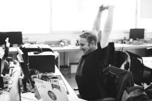 escritório com uma pessoa esticando os braços e impressora na mesa